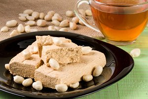 peanut halva in the plate on a green wooden background