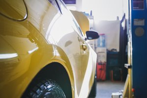 Yellow car in garage auto service - diagnostics and repairing