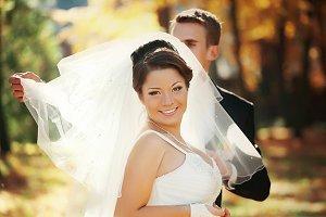 Groom spreads bride's veil