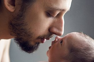 father is holding a little newborn son head to head