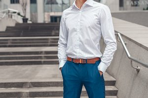 Businessman holds hands in his trouser pockets