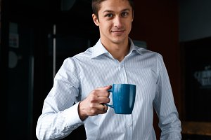 Charming young male with cup of coffee