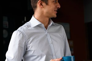 Coffee break. Confident young handsome man in blue pants