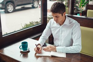 Handsome young businessman working and writing something