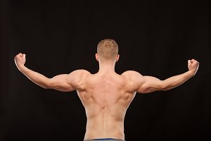 Athletic handsome sportsman fitness-model showing his muscular back. isolated on black background with copyspace