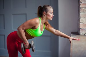 The beautiful healthy girl pumps muscles using dumbbell at the gym.