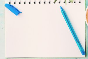 Blank notebook white page with blue pen and flowers