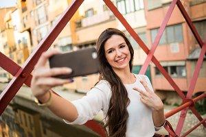 Young girl taking selfie on bridge