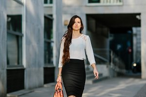 Confident young lady walking down street