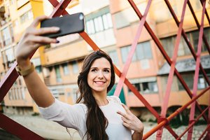 Young girl taking selfie on bridge