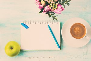 Blank notebook page with blue pen and cup coffee flowers