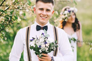 Portrait of the groom with a bouquet