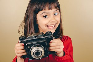 Funny little retro photographer girl