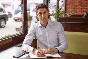 Portrait of an handsome business man working in cafe
