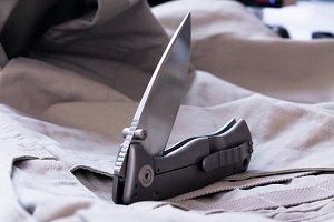 Pocket knife on cloth background.