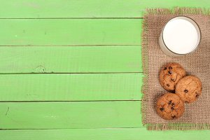 glass of milk with oatmeal cookies on a green wooden background with copy space for your text. Top view