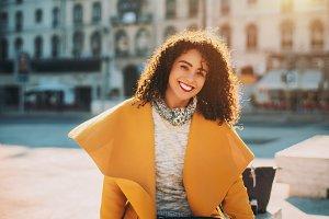 Curly Brazilian girl in yellow coat