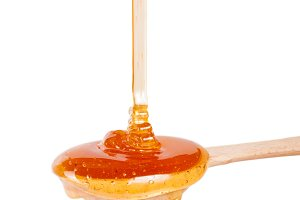 Honey in a wooden spoon isolated on a white background
