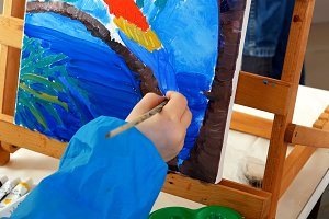 Little girl paints oils picture with brush