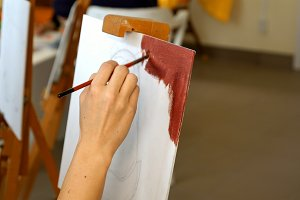 Female artist paints picture artwork in art studio