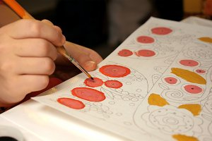 Child paints watercolor picture with paint brush