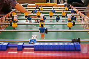 Father and child play kicker table football soccer