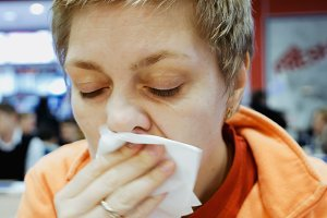 Young woman wipes her mouth with napkin in a cafe