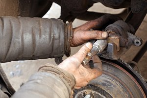 Auto mechanic working on brakes in car repair shop