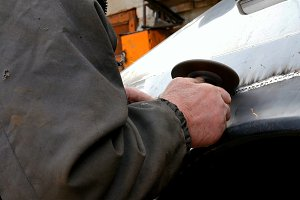 Auto mechanic working on a car body in garage