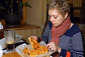 Pretty blond woman eats pizza and drinks beer