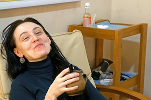 Smiley woman relaxes in armchair with cup of tea