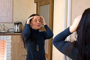 Pretty long hair woman applies cream on her face