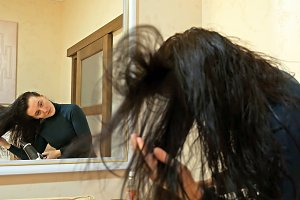 Pretty woman drying long hair in make-up room