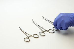 Surgical nurse puts medical surgery tools on table
