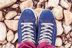 Feet with dirty blue urban shoes