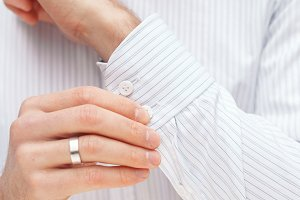 Man buttons cuff-link on French cuffs sleeves