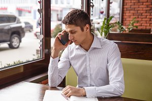 Young businessman in a suit working and talking on the phone