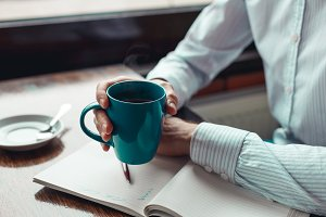 Close up coffee break businessman hands holding mug of coffee