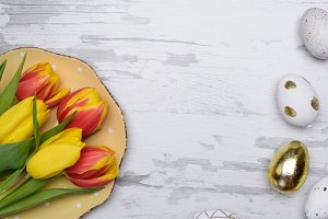 Easter eggs and tulips over wooden background.