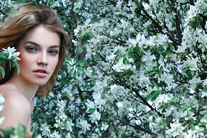 Beautiful girl among white flowers.