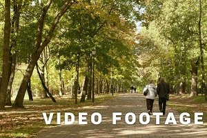 Adult couple walks in the park. Autumn daytime. Smooth dolly shot