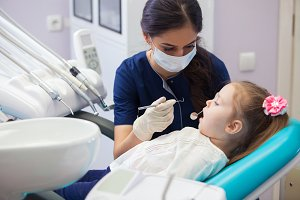 female dentist in mask treats teeth little girl