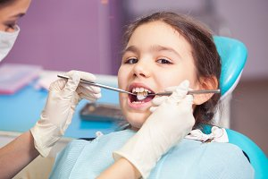 Close-up of pretty little girl opening his mouth wide during treating her teeth by the dentist