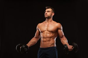 Handsome athletic man in gym is pumping up muscles with dumbbells in a gym. Fitness muscular body isolated on dark background.