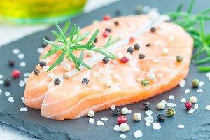 Fresh raw salmon steak with seasonings on stone board, horizontal