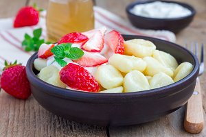 "Traditional russian, ukrainian cottage cheese ""lazy"" dumplings served with yogurt, honey and strawberry, horizontal"