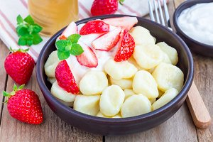 "Traditional russian, ukrainian cottage cheese ""lazy"" dumplings served with yogurt, honey and strawberry, horizontal"