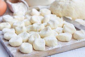 "Making traditional russian, ukrainian cottage cheese ""lazy"" dumplings, raw dumplings on wooden board, horizontal"