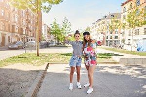Two friendly young women standing waving