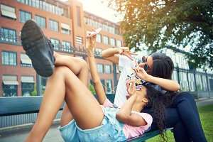 Woman stretched on bench with friend take photo
